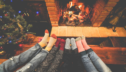 Feet view of happy family lying down next fire place and christmas tree wearing warm wool socks -...
