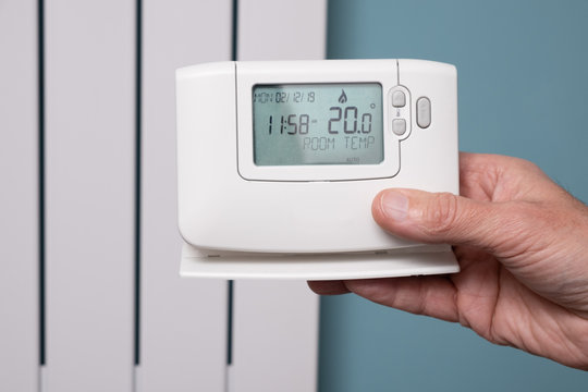 Hand holding central heating controller with modern radiator panel in background