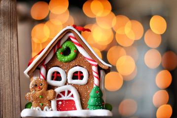 Christmas decorations with colorful gingerbread house with beautiful bokeh lights garland closeup picture. Winter holidays new year and xmas composition