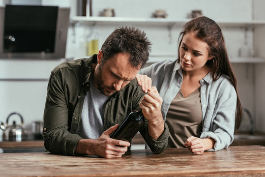 Woman supporting alcohol addiction husband with wine bottle on kitchen