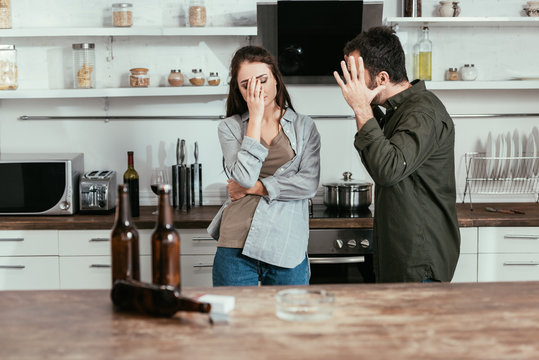 Selective focus of angry man quarreling with alcohol addicted wife on kitchen