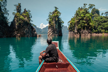 Tourist man sitting on a typical boat of thailand. Khao Sok National Park