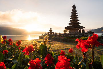 Beautiful famous touristic pagoda in Bali. Pura Ulun Danu Pagoda during the sunrise with red flowers