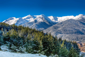 Houses, forest and snow Pirin mountains landscape panorama in bulgarian ski resort Bansko, Bulgaria