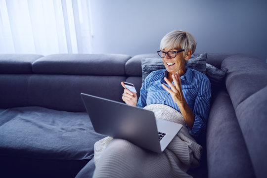 Cheerful charming caucasian senior blond woman with short hair and with eyeglasses sitting on sofa in living room, holding laptop in lap and using credit card for online shopping.