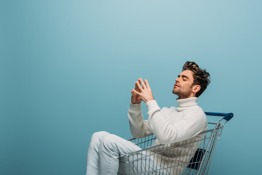 thoughtful man sitting in shopping cart, isolated on blue