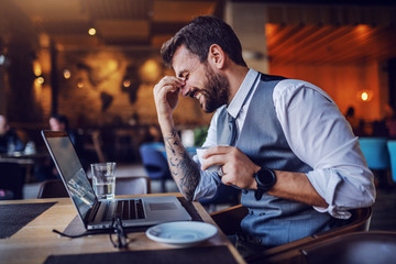 Good-looking smiling caucasian bearded businessman in suit sitting in cafe, holding cup with coffee and laughing. On table are glasses, laptop and water. Fotobehang