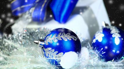 Christmas gift and blue balls on black festive background