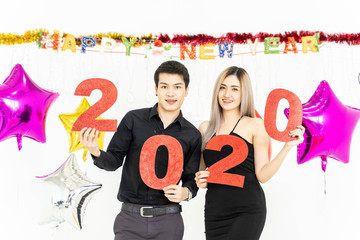 Delighted Asian man and woman with golden 2020 balloons smiling and looking at camera while standing under Happy New Year writing and tinsel