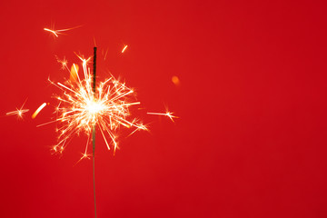 Close up of Brightly burning sparkler on a red background with lots of sparks.