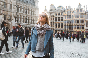 Woman stands in the square Grand Place in Brussels, Belgium at sunset.