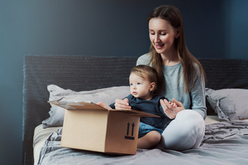 Woman and little child enjoying their new things delivered from international online store. Family goods ordered on internet from big trusted retailers. High-quality products at affordable prices.