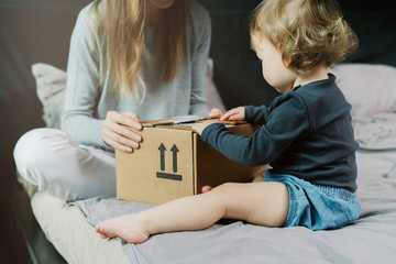 Baby and woman sitting on bed and opening a mail box with products ordered on Internet. Online retailers offering wide range of goods delivered to your home address. Safe and quick shipping worldwide.