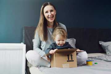 Young mother laughing at baby getting into cardboard package box. Toys received from online shop. Quick delivery of high-quality goods. Protection of online payments with bank card. Trusted delivery.