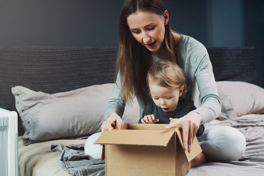 Woman and baby unpacking cardboard box with surprise. International shopping with shipment worldwide. Great range of high-quality products delivered from best sellers to your home address by mail.