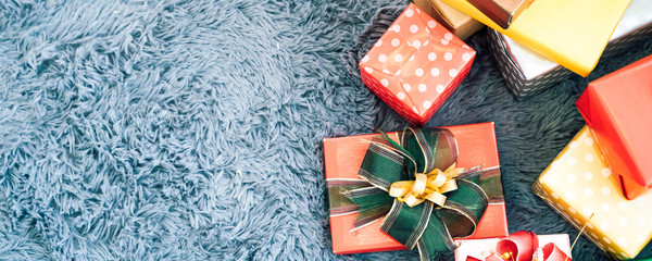 Horizontal top view of colorful gift boxes with ribbons over rustic background - with copy space