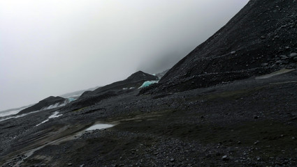 Keuken foto achterwand Grijze traf. Overcast weather glacier hiking in Iceland volcanic black stone landscape with ice and snow