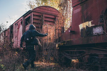 Homeless immigrant with hoodie jumping on old train wagons