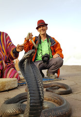 Happy tourist taking pictures with snakes