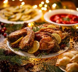 Christmas carp, fried carp fish slices on a ceramic plate on the holiday table, close up. Traditional christmas eve dish. Polish Christmas