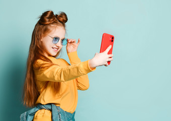 A beautiful red-haired girl takes a selfie with a new mobile phone in a red case. In blue glasses and a yellow sweater