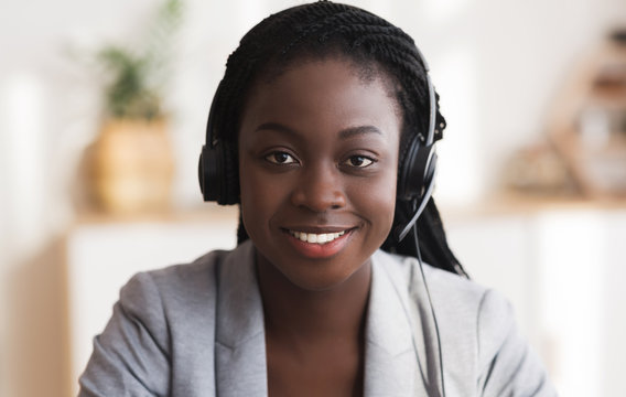 Portrait of black smiling female call center operator in headset