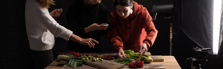 cropped view of photographers making food composition for commercial photography on smartphone, panoramic shot