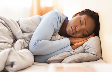 Wall Mural - Black Girl Sleeping Holding Folded Hands Near Face In Bedroom