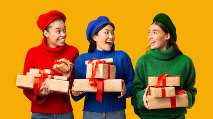 Three Multiethnic Women Holding Wrapped Gifts Standing, Yellow Background