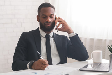 Black businessman talking on mobile phone while working in office
