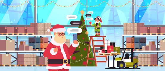 santa with male elf helper chatting using mobile app on smartphone social network chat bubble communication concept modern warehouse interior portrait horizontal vector illustration