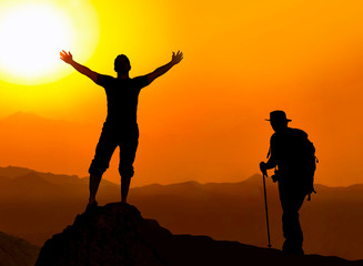 Happy celebrating winning success man at sunset or sunrise standing elated with arms raised up above her head in celebration of having reached mountain top summit goal during hiking travel trek.