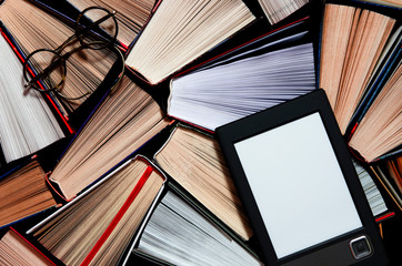 The e-book with a white screen lies on the open multi-colored books that lie on a dark background, close-up