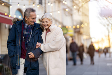 Senior couple walking on the city street at winter day