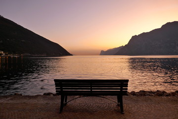 Lonely wooden bench by the lake after sunset