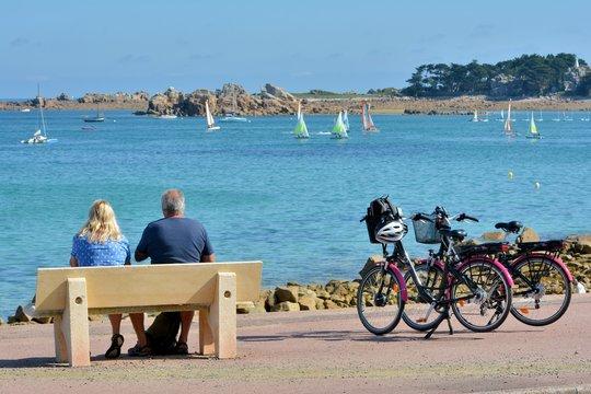 Couple de pensionnés pratiquant le vélo assis sur un banc ace à la mer en Bretagne