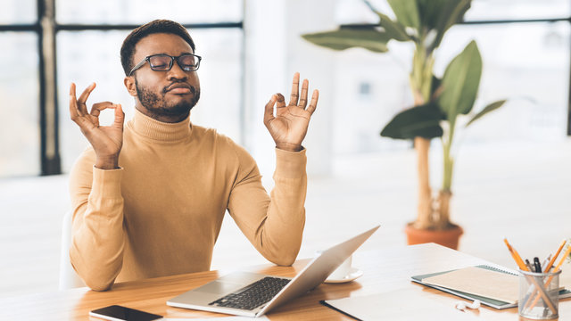 Calm black guy meditating while doing homework