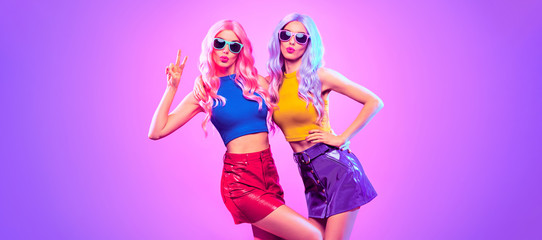 Wall Mural - Gorgeous Disco Party girl with Having Fun, neon style. Pink Purple hairstyle. High Fashion. Two young beautiful model woman friends Dance, colorful neon Light. Night Clubbing.Pop Art fashionable Style