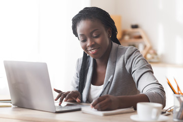 Black businesswoman working in office, typing on laptop and taking notes