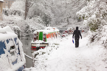 Woman walking in heavy snow on the Kennet and Avon towpath in Bath, England, UJK.