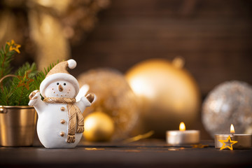 Christmas golden decorations and snowman on dark wooden backgrou