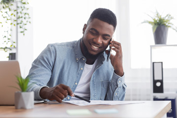 African businessman talking with companion on phone and checking financial reports