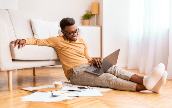 Happy afro entrepreneur working on laptop sitting on floor indoor