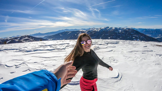 A girl holding a man's hand on a snowy background in Bad Kleinkirchheim, Austria. Follow me to winter wonderland! She is happy, having fun. There is a lot of snow caped mountain in the back.