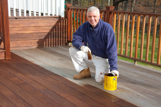 painter staining a deck in the spring