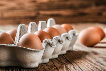 Eggs in basket. Brown chicken egges on wooden vintage table. Fresh egg on morning breakfast.