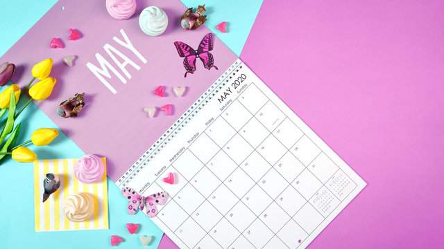 On-trend 2020 calendar page for the month of May modern flat lay with seasonal food, candy and colorful decorations in popular pastel colors. Copy space. One of a series for 12 months of the year.