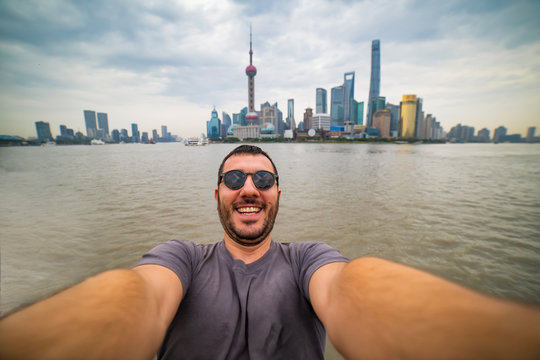 Happy tourist man take selfie with Shanghai skyline, handsome similing man traveling in China