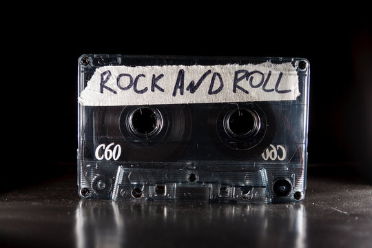 vintage old film music cassette isolated on black background with the inscription rock and roll, background music, music lovers