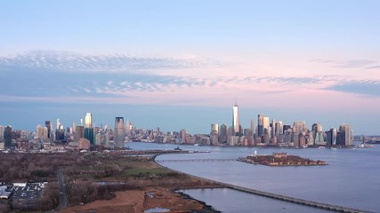Fotomurales - Aerial footage of New York City and Jersey City skylines together with Ellis Island, as viewed from above Liberty State Park, in New Jersey, at dusk, with slow forward camera movement.